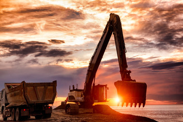 backhoe or digger working with bucket at industrial earth excavation site loading dump truck in sunrise light