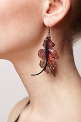 Beautiful woman with galvanic earring in form of oak leaf