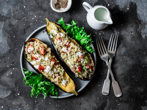 Grilled eggplant stuffed with couscous, tomatoes, cilantro with yogurt sauce on a dark background, top view