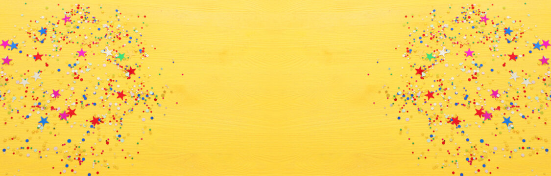 Party colorful confetti over yellow wooden background . Top view, flat lay