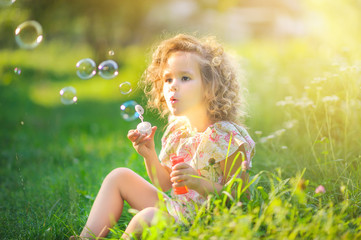 Cute girl blows soap bubbles while sitting on the grass in the park at sunset. Children's fun.. Wall mural