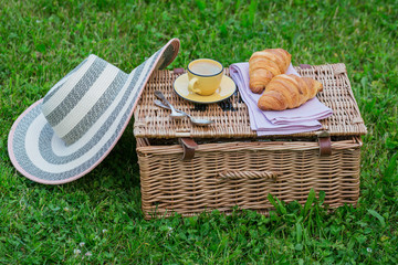 Picnic at the park on the grass: wicker basket, fresh croissants and coffee