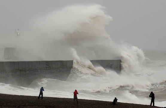 People view large waves caused by Storm Ciara as they hit the the seafront and wall in Newhaven