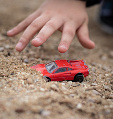Red toy car in the sand is found by a kid. The picture shows how a kid hand is grabbing a toy car found in the sand in a public park.