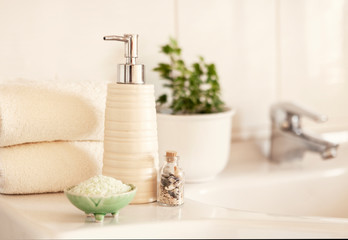 Foto op Canvas Spa Ceramic soap, shampoo bottle, bowl with bath salt and white cotton towels on Blurred bathroom interior background with sink and faucet.