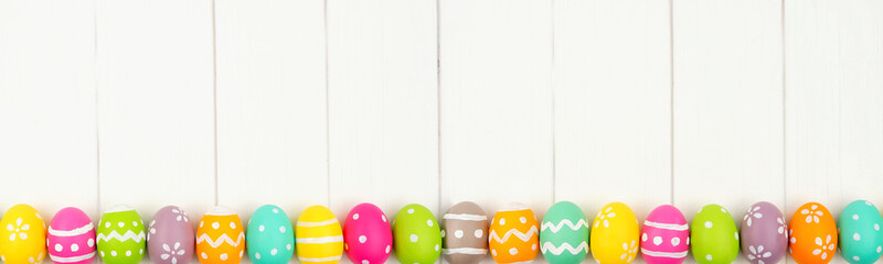 Wall Mural - Colorful Easter banner with row border of Easter Eggs against a white wood background. Overhead view with copy space.