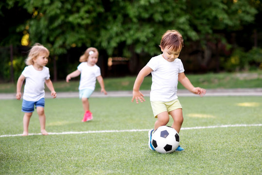 Football game: team of toddlers playing soccer on green field: three children, two boys (one is barefoot) and girl playing at stadium, smiling little boy dribbling ball is running in front place