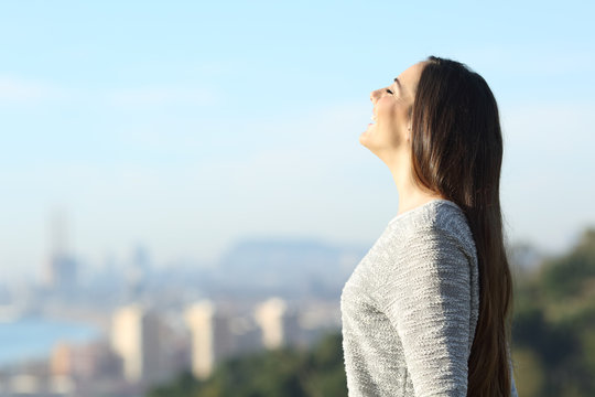 Happy woman breathing fresh air with a city in the background
