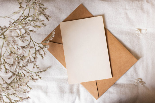 mockup card with plants. invitation card with envelope and details Mockup with postcard and flowers on white background.
