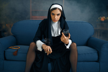 Sexy nun in a cassock sitting spreading her legs
