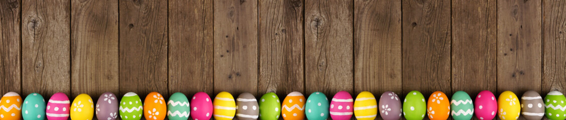 Wall Mural - Colorful Easter banner with row of eggs bottom border over a rustic old wood background. Top view with copy space.