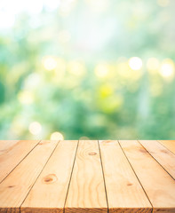 Poster Tuin Real wood table top texture on blur leaf tree garden background