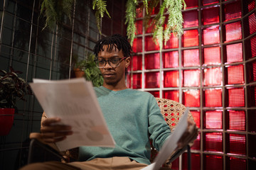 Portrait of contemporary African man working with documents while sitting in cafe lounge, copy space