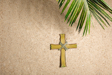 Wall Mural - Cross and Palm Tree Leaves on sand. Palm sunday concept. Top view