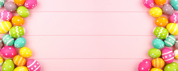 Wall Mural - Colorful Easter banner with double sided Easter Egg border against a pink wood background. Top view with copy space.