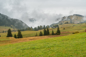 Dolomites mountain landscape cover with low cloud in autumn in Alpe di siusi, Italy