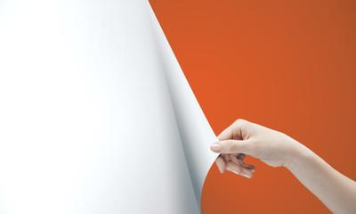 Woman hand turning orange page