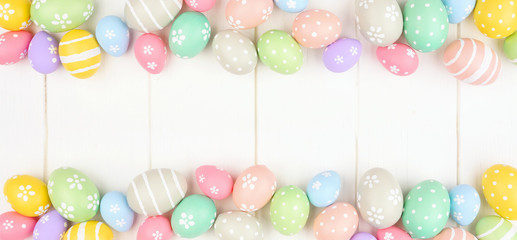 Wall Mural - Pastel colored Easter Egg banner with double border against a white wood background. Above view with copy space.