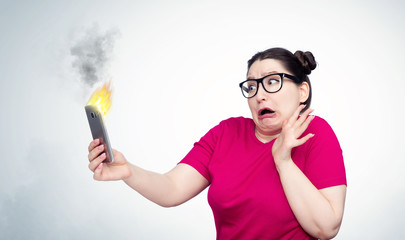 Young emotional girl with fear looks at a smartphone burning in her hands. The situation with fire phone batteries.