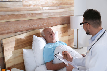 Doctor examining senior patient in modern hospital