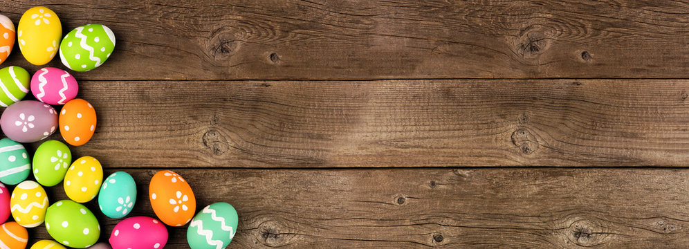 Colorful Easter Egg banner with corner border against a rustic old wood background. Top view with copy space.