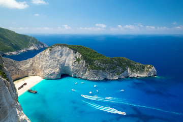 Papiers peints Navire Picturesque top view of Navagio Beach or Shipwreck Beach. Old ship after crash on sand in lagoon surrounded by high rocks. Boats floating turquoise Ionian Sea. Paradise in Zakynthos island, Greece