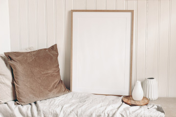Portrait empty wooden frame mockup with linen cloth, velvet cushions and modern ceramic vases. White beadboard wainscot wall paneling background. Scandinavian interior, home design. Art concept.