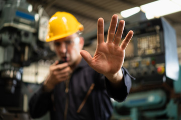 Selective focus of industrial worker in factory site gesture keep out while communicating with a walkie talkie, concept restricts access in industrial factory, working profession, factory restriction.