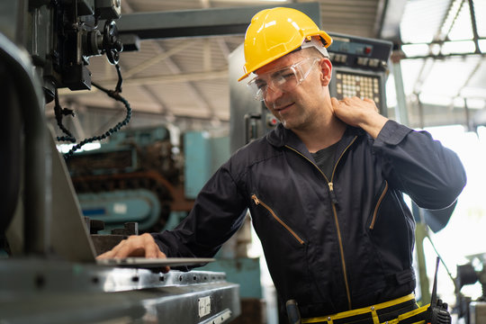 Exhausted factory worker rubs his shoulder due to the back and shoulder aches shows pain expression face, concept working exhaustion, factory worker lifestyle, office syndrome, tiring work hour.