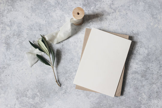 Feminine wedding stationery, desktop mock-up scene. Blank greeting card, craft envelope with olive branch and silk ribbon.Grunge table background. Flat lay, top view. Italian summer design.