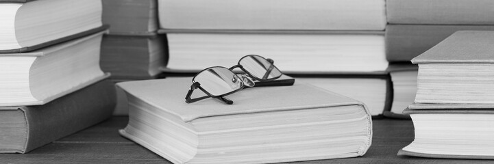 glasses lie on one of the thick books lying in a pile