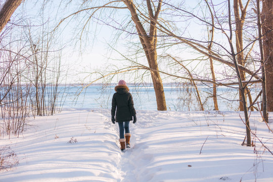 Winter hike woman walking in snow forest nature park by the river. Cold weather outerwear girl wearing warm down coat jacket and wool hat and boots.
