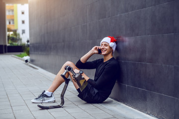 Fotomurales - Cheerful Caucasian sportsman with artificial leg and with santa hat on head sitting on ground, leaning on wall and talking on the phone.