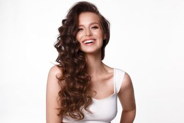 Obraz Beautiful young girl in white dress with natural make-up, hair curls and smile. - fototapety do salonu
