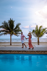 couple on the beach with palm tree and swimming pool in Thailand Chumphon area during sunset at Arunothai beach