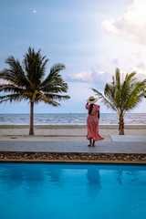 woman on the beach with palm tree and swimming pool in Thailand Chumphon area during sunset at Arunothai beach