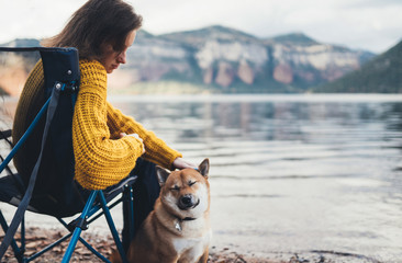 tourist traveler girl relax together friends dog closed eyes on background mountain landscape,  woman hugging pet rest on lake shore nature trip