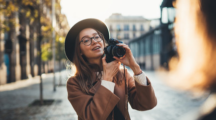 Hobby photographer concept. Outdoor lifestyle portrait of smiling  woman having fun in sun city in Europe with camera travel photo of photographer in glasses and hat take photo model