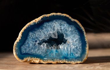 Geode with transparent crystals of light-blue color on a dark background..