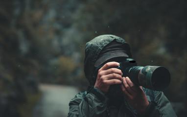 Hombre tomando una fotografía bajo la lluvia