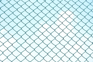 Close up green square wire mesh chain link fence against blue sky white clouds for background texture