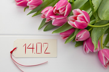 Vlentine's Day card and a bouquet of beautiful tulips on wooden background.
