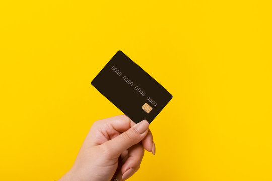 Female hand holding credit card on yellow background