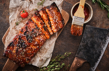 Delicious barbecued ribs seasoned with a spicy basting sauce and served on chopping board.