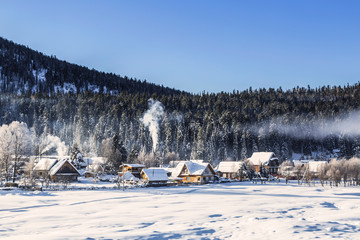 View of the winter  the village Iogach against the background of forested mountains. Altai Republic, Russia