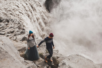 Young stylish couple in love walking together near famous Icelandic Dettifoss waterfall. Traditional wool sweaters, hat, red hair, gray skirt. Dramatic nordic landscape, cold weather in Iceland