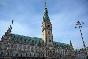 Historical town hall with clock tower in the city of Hamburg against a blue sky with clouds