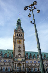 Clock tower of the historic town hall in the city of Hamburg against a blue sky with clouds