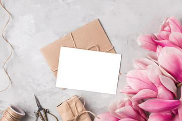 Creative layout made with pink magnolia flowers, greeting card, gift box and rope on gray...