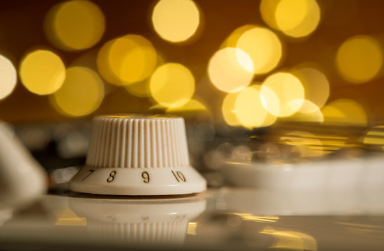 Macro of a white electric guitar volume knob on 9 with abstract bokeh lights in the background. Side view, flat.